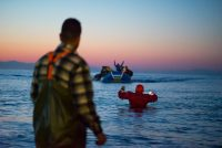 """My friend Paco from ""Proem Aid"" wades out into the water to bring in a punctured boat. One of those moments of heroism that happens everyday in the refugee crisis. These inspiring and positive human stories are often under reported. Paco is a 50 year old unpaid Spanish firefighter."""